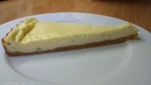 Ein Stück fertiger Cheesecake auf einem weißen Teller