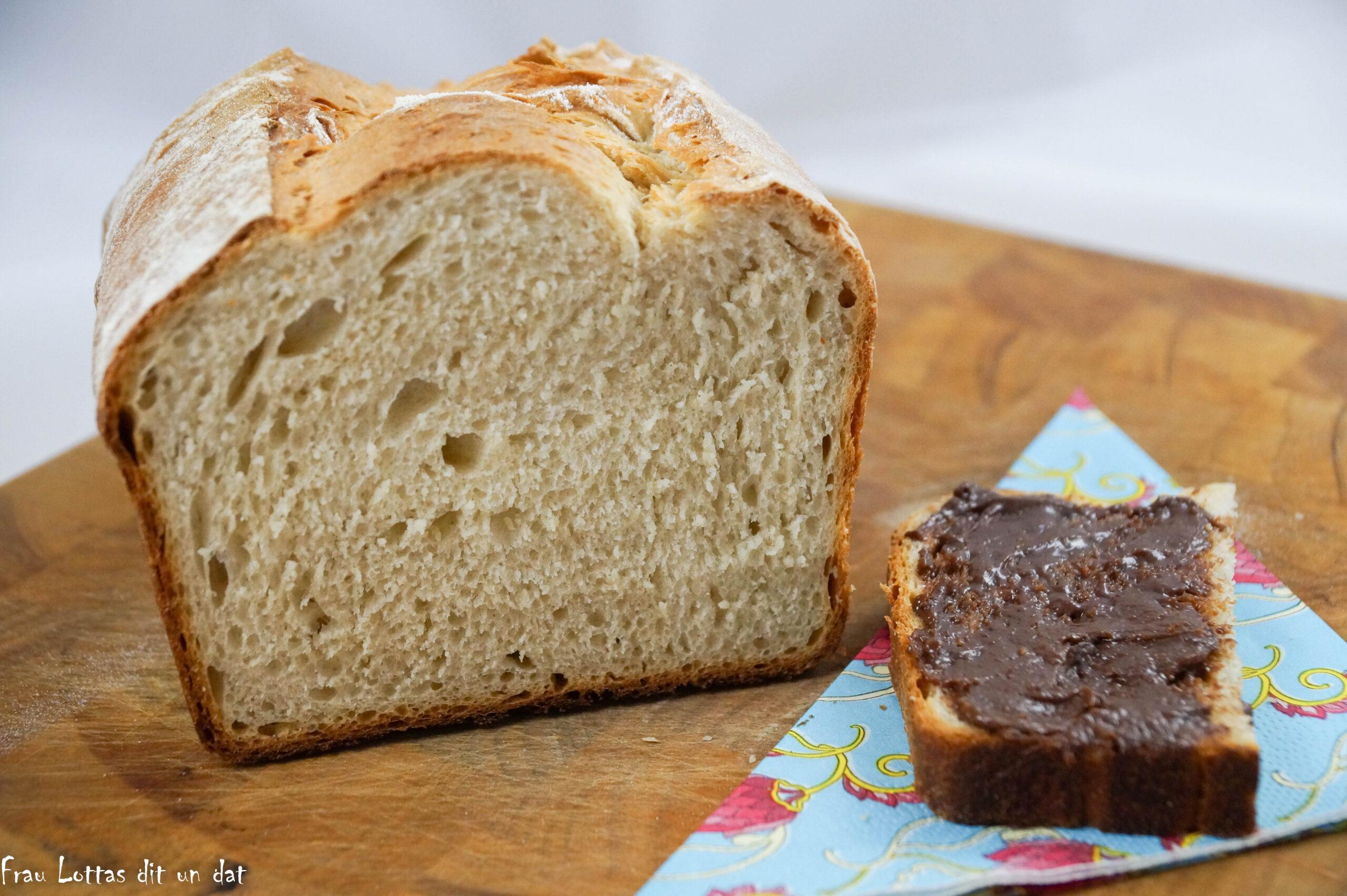 Aufgeschnittenes Toast, daneben eine halbe Scheibe beschmiert mit Schokocreme