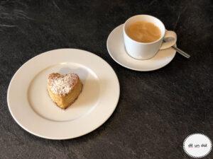 Teller mit einem Feigenherzküchlein und daneben eine Tasse Kaffee auf einer Untertasse