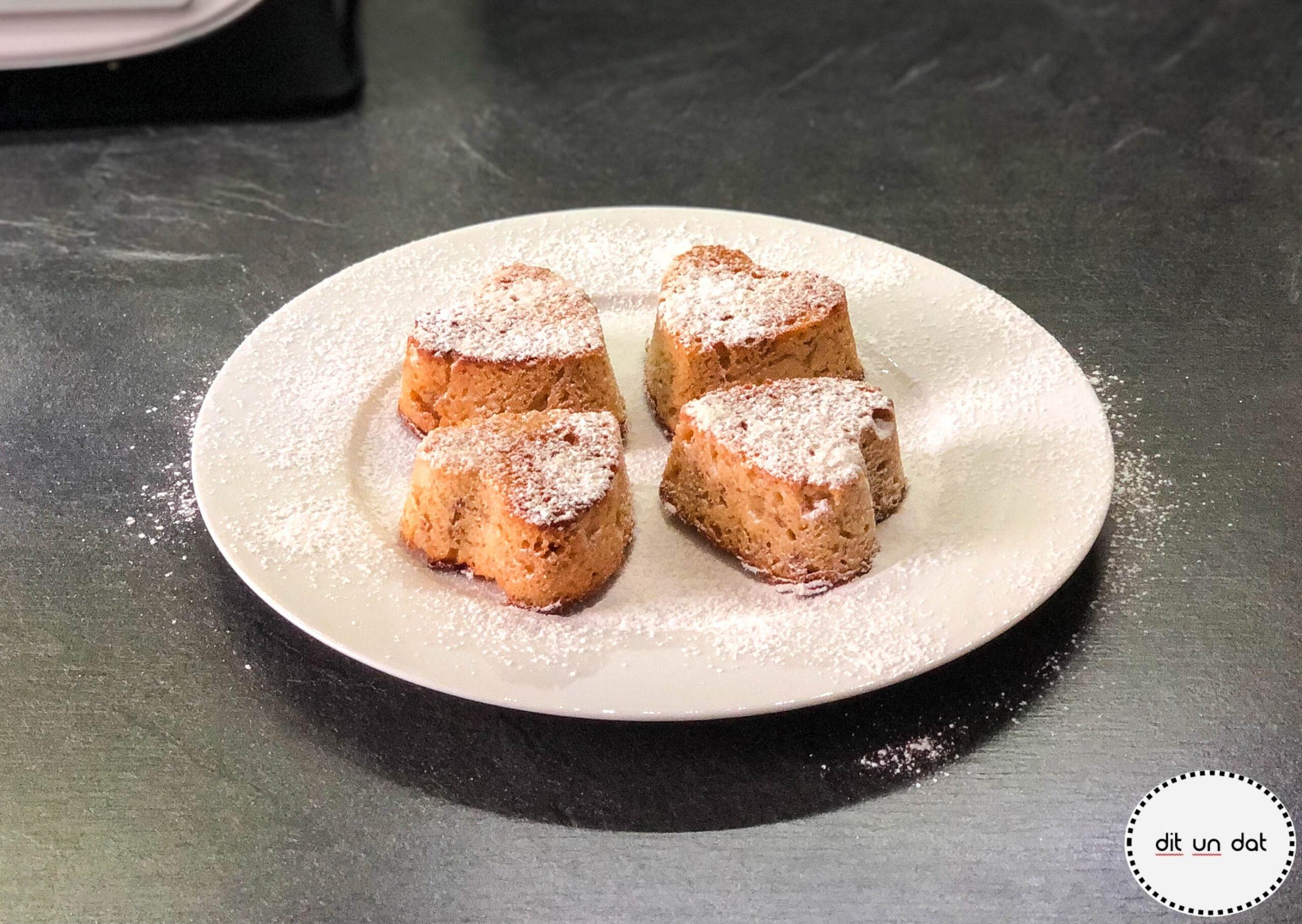 Ein Teller mit vier Feigenherzküchlein. Die spitzen innen zueinander angeordnet, mit Puderzucker bestäubbt.