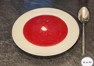 Ein weißer Teller mit Roter Beete Suppe und einem weißen Klecks Merrettich