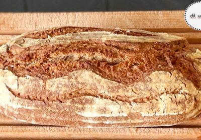 Fertig gebackenes längliches Brot auf einem Hlzgitterbrett.
